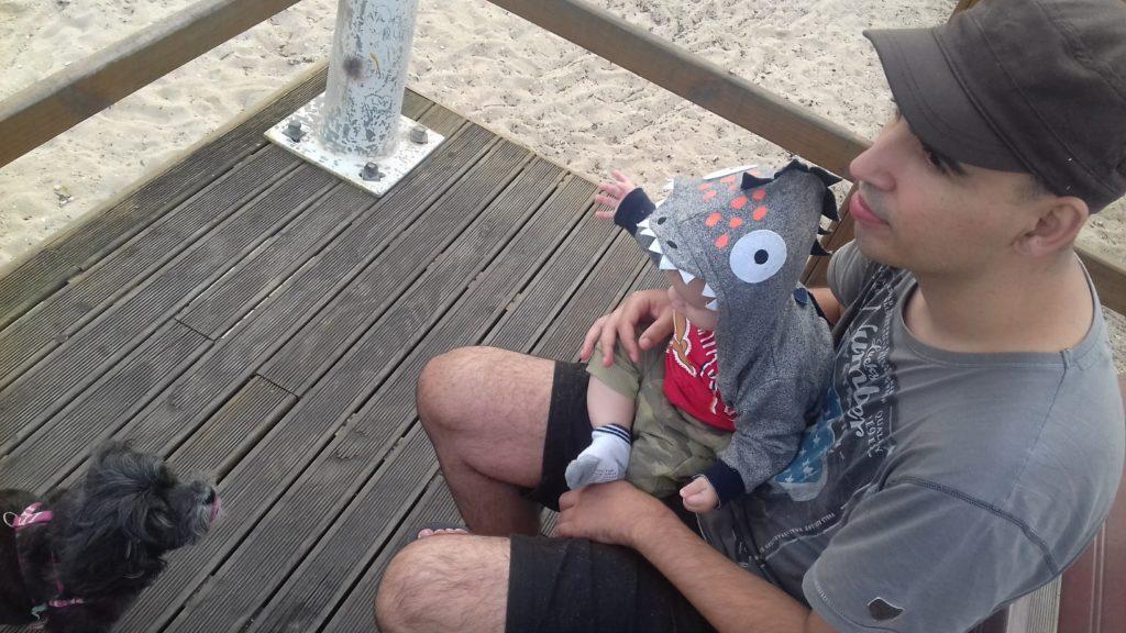 Papai com o filho no colo em um deque de madeira na beira mar de São José